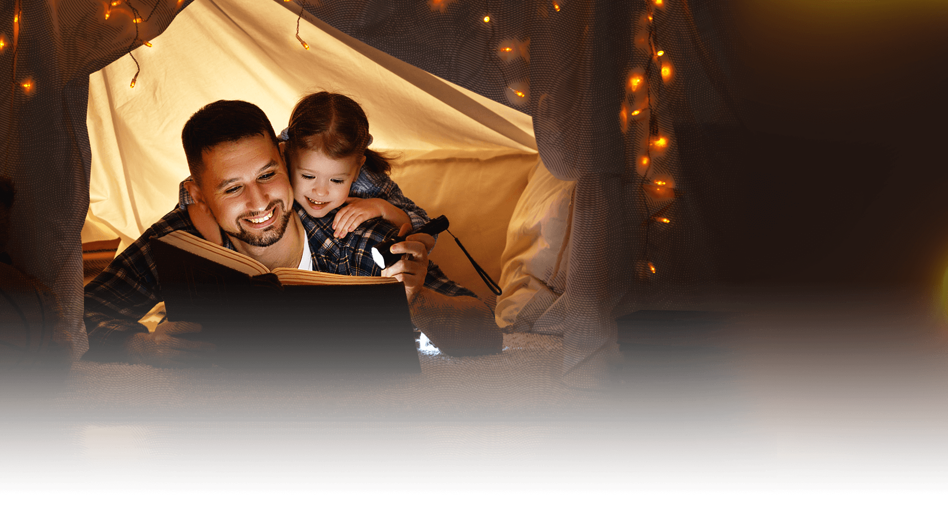 Young father reading with his daughter in a tent